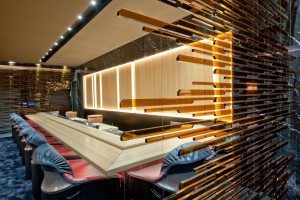 L'illuminazione del banco sushi lungo più di sei metri intorno al quale è possibile sedersi ed essere serviti di fronte ai cuochi che cucinano.